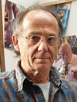 artist don faulkner wearing blue open neck shirt in own studio with images in the background